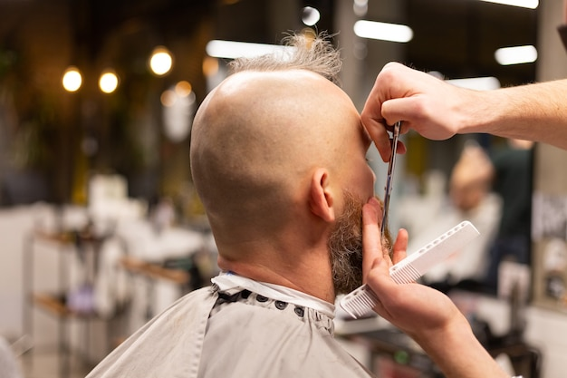 Europejski brutalny mężczyzna z obciętą brodą w zakładzie fryzjerskim