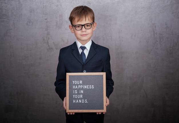 Europejski chłopiec w marynarce i krawacie, trzymając znak z tekstem w języku angielskim