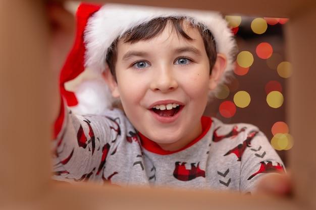 Europejski chłopiec w świątecznym swetrze i mikołaju
