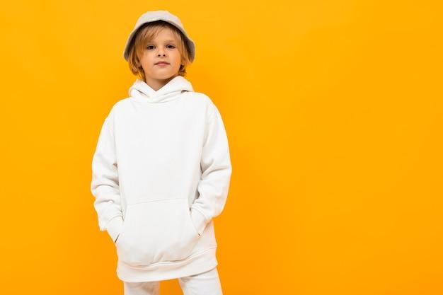 Europejski chłopiec z panamą w białej bluzie z kapturem na żółtym tle.
