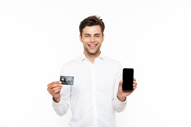 Europejski facet z ciemnymi włosami, trzymając smartfon i kartę kredytową