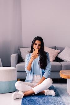 Europejski fit brunetka moda blogger kobieta siedzi na podłodze w salonie obok sofy z telefonem