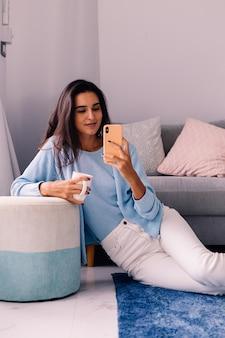 Europejski fit brunetka moda blogger kobieta siedzi na podłodze w salonie obok sofy