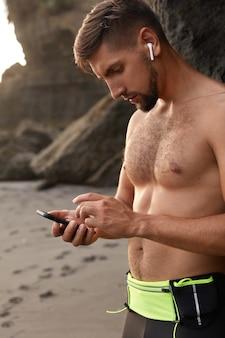 Europejski jogger robi sobie przerwę, korzysta z nowoczesnej sieci komórkowej, pobiera utwory z playlisty na trening