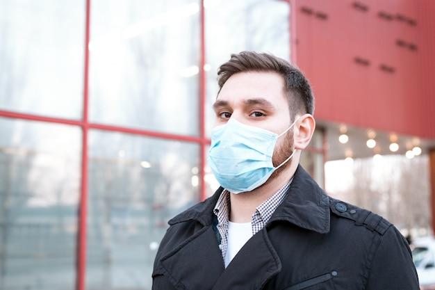 Europejski koronawirus. portret kaukaski mężczyzna ubrany w maskę higieniczną twarzy, maska do ochrony dróg oddechowych na zewnątrz.