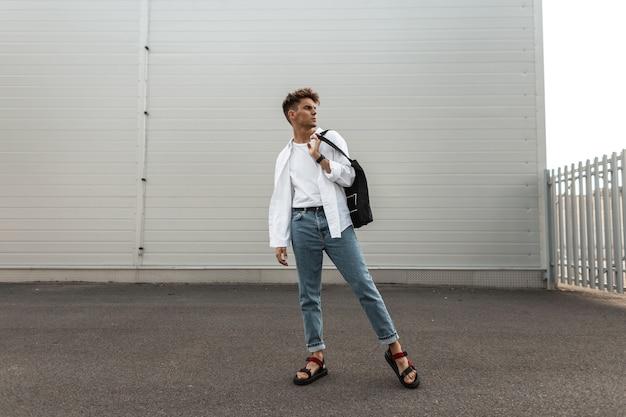 Europejski model młodego człowieka w stylowe ubrania w skórzane czerwone sandały z czarną torbą