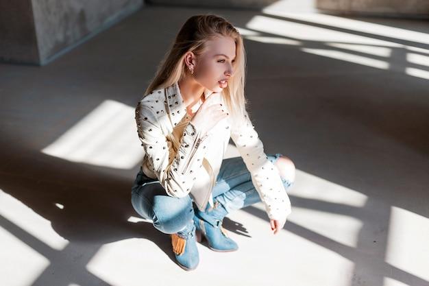 Europejski model młodej kobiety w vintage skórzanej kurtce w niebieskich modnych zgranych dżinsach w zielonych modnych kowbojskich butach pozujących siedząc w pomieszczeniu z promieniami słonecznymi