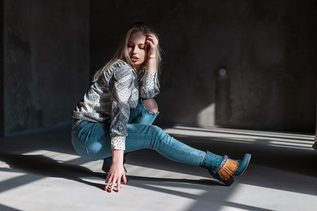 Europejski model modnej młodej kobiety w stylowe dżinsy w zielonych modnych kowbojskich butach w modnej koszuli pozuje siedząc w pokoju ze światłem słonecznym