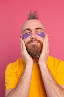 Europejski przystojny brodaty mężczyzna w żółtej koszulce i fioletowej masce na oczy na różowo