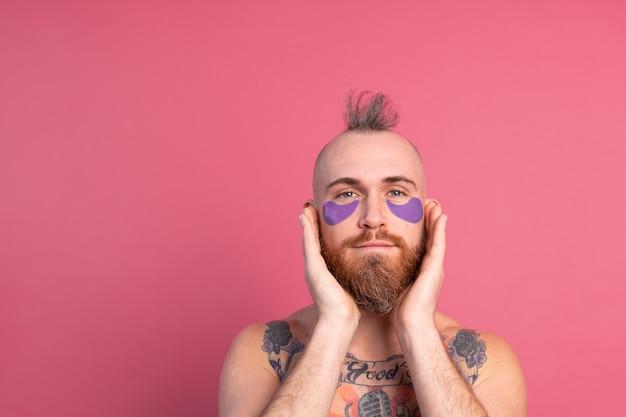 Europejski przystojny brodaty wytatuowany topless mężczyzna z fioletową maską na oczy pozuje do aparatu na różowo