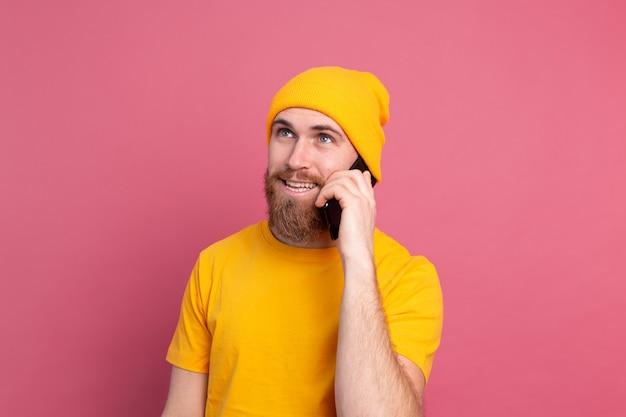 Europejski przystojny szczęśliwy wesoły mężczyzna rozmawia na smartfonie uśmiechając się na różowo