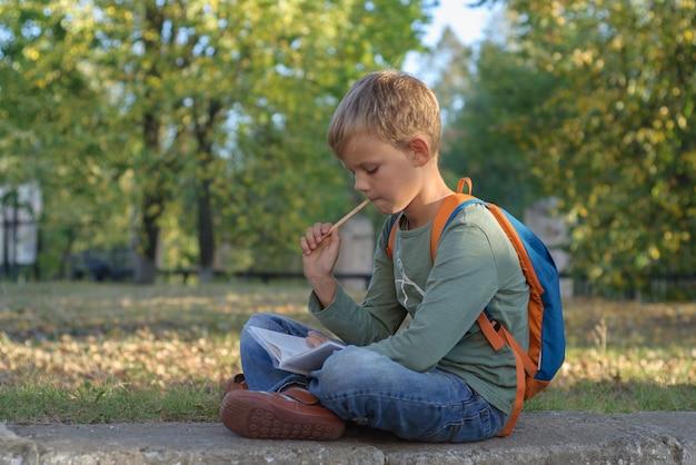 Europejski uczeń chłopiec odrabiania lekcji w zeszycie, siedząc w pięknym jesiennym parku