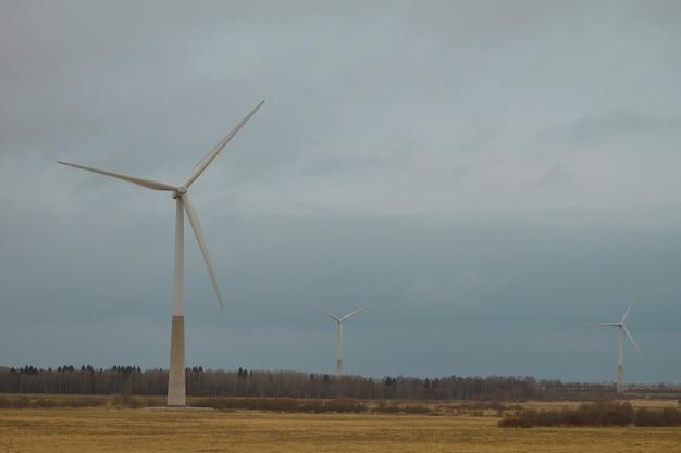 Europejskie farmy wiatrowe na tle jesienny krajobraz z pochmurną pogodą.
