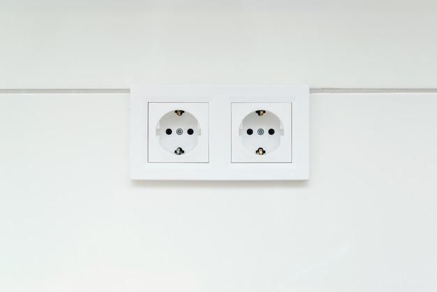 Europejskie gniazdko elektryczne na białej ścianie i gniazdo standard ue.