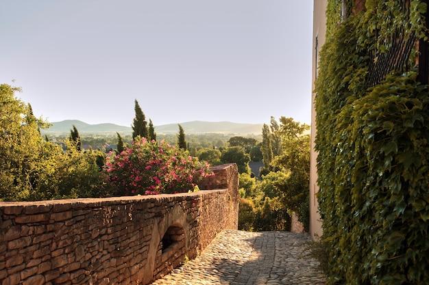 Europejskie stare miasto z wąską uliczką dla pieszych i kamienną brukowaną w barjac o zachodzie słońca we francji