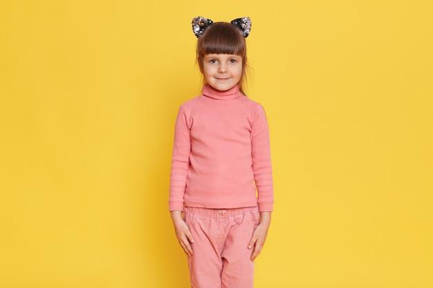 Europejskie urocze małe dziecko płci żeńskiej pozuje z uszami kota na żółtym tle