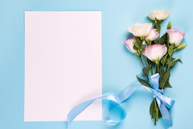 Eustoma kwitnie z papierowym prześcieradłem na błękitnej powierzchni, odgórny widok.