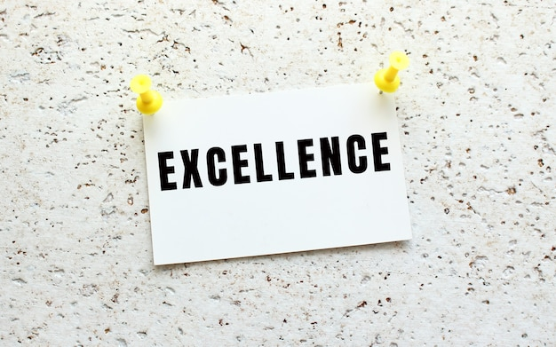 Excellence jest napisane na karcie przyczepionej do białej, teksturowanej ściany za pomocą guzika. przypomnienie o biurze. pomysł na biznes.