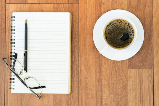 Eyeglasse i notatnik z filiżanką kawy na pokładzie drewna
