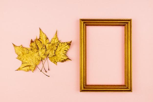 F pozłacane liście klonu i drewniana ramka na zdjęcia na różowo