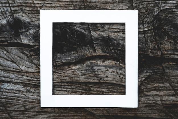 F widok z góry białej kwadratowej ramki na wierzchu ciemnej drewnianej porysowanej powierzchni