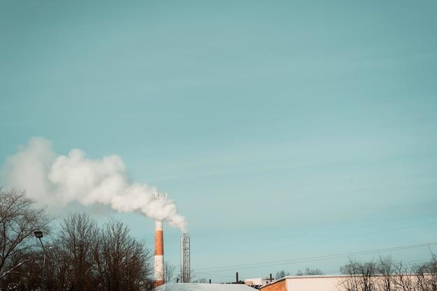 Fabryczne kominy dymią w mieście na tle błękitnego nieba. zanieczyszczenie środowiska. skopiuj miejsce