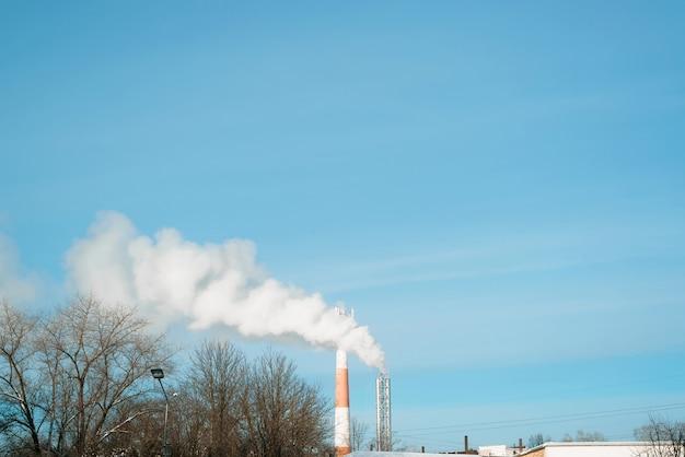 Fabryczne kominy dymią w mieście na tle błękitnego nieba. zanieczyszczenie środowiska