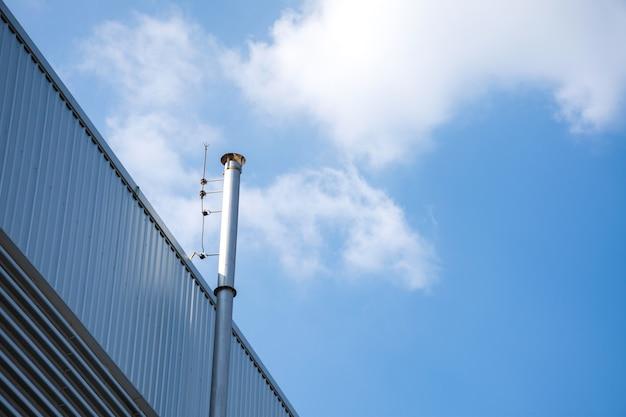 Fabryka dymu komina z błękitnym niebem i chmurami.