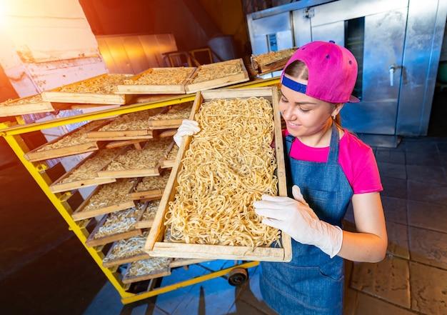 Fabryka makaronów do produkcji wyrobów mącznych. produkcja technologiczna makaronów. praca przemysłowa w fabryce, zbliżenie surowego makaronu.