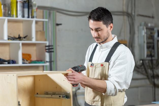Fabryka mebli, koncepcja małych firm i ludzi - młody pracownik pracuje w fabryce przy produkcji mebli.