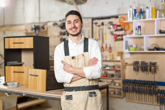 Fabryka mebli, małe firmy i koncepcja ludzi - portret uśmiechniętego mężczyzny pracownika w produkcji.