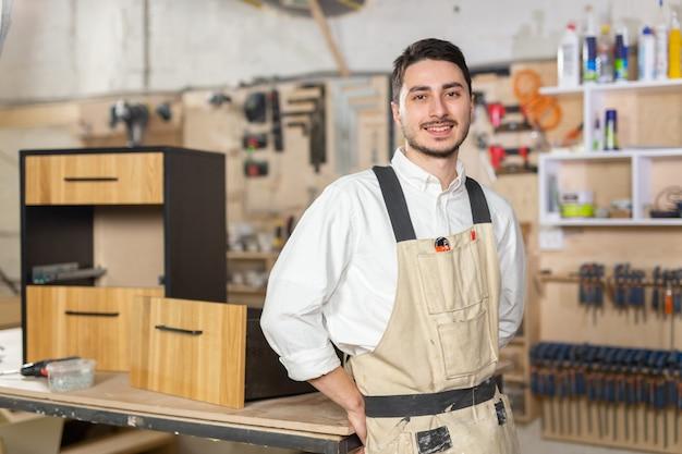 Fabryka mebli, małe firmy i koncepcja ludzi - portret uśmiechniętego pracownika płci męskiej przy ul