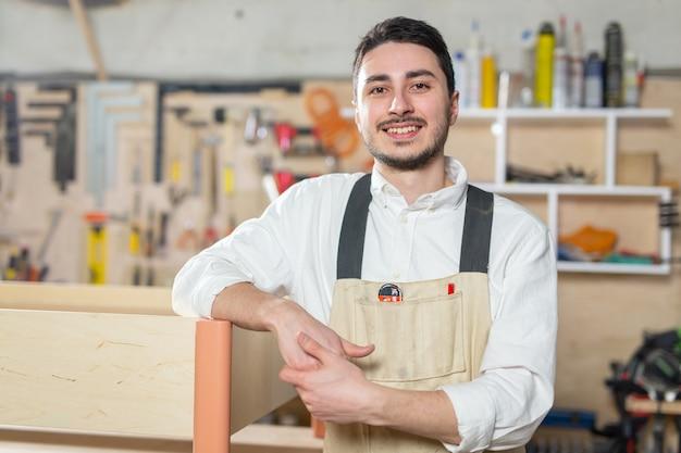Fabryka mebli, małe firmy, koncepcja biznesowa - mężczyzna robotnik przy produkcji mebli