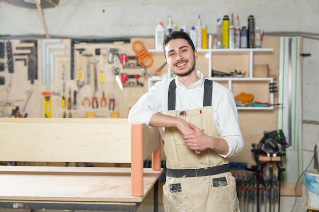 Fabryka mebli, małe firmy, koncepcja biznesowa - mężczyzna robotnik przy produkcji mebli.