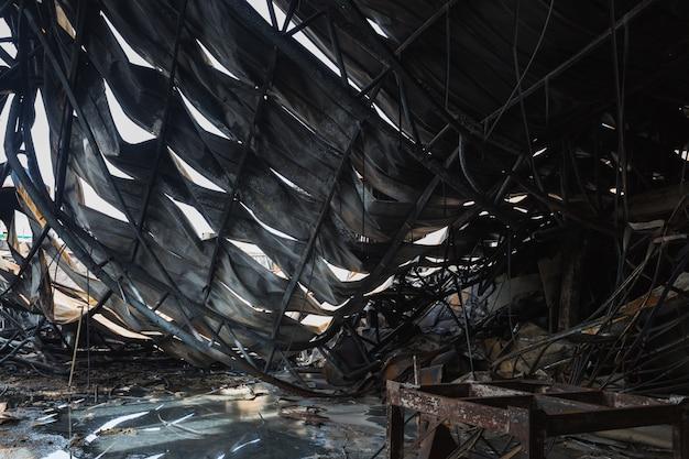 Fabryka po pożarze. spalony magazyn ze zwęglonymi wiązarami dachowymi i wypalonymi produktami