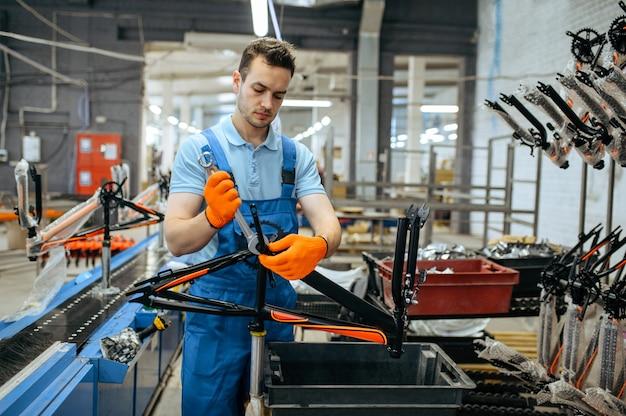 Fabryka rowerów, pracownik trzyma czarną ramę roweru dla nastolatków. męski mechanik w mundurze instaluje części rowerowe, linię montażową w warsztacie