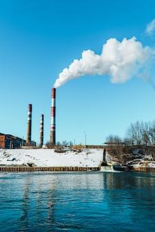 Fabryka wypuszcza przez dużą rurę biały dym zanieczyszczeń