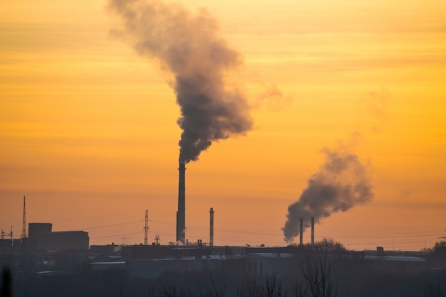 Fabryka z rurami i dymem o świcie słońca.