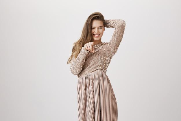 Fabuloud kobieta wskazując aparat w luksusowej sukience