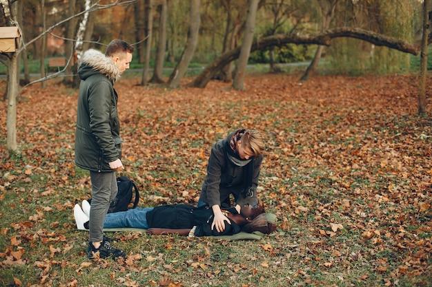 Faceci pomagają kobiecie. afrykańska dziewczyna leży nieprzytomna. udzielanie pierwszej pomocy w parku.