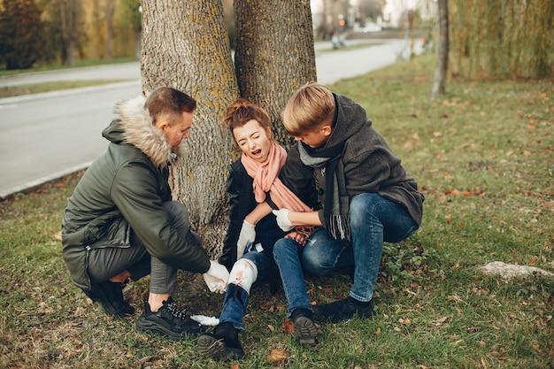 Faceci pomagają kobiecie. dziewczyna ze złamaną nogą. udzielanie pierwszej pomocy w parku.