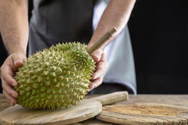 Faceci trzymają w ręku durain króla owoców na drewnianym tle