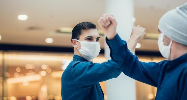 Faceci W Ochronnych Maskach Witają Się Na Spotkaniu. Zdjęcie Z Miejsca Kopiowania Premium Zdjęcia