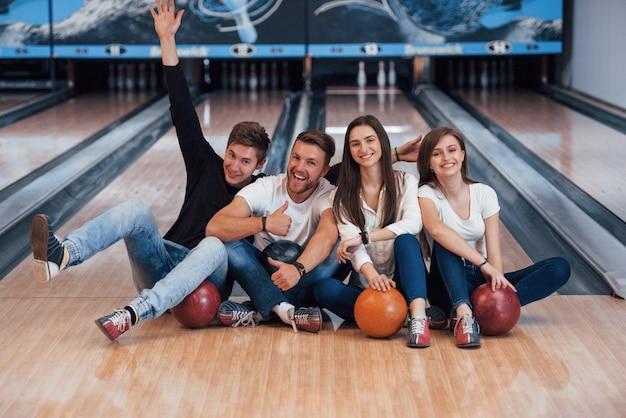 Facet baw się dobrze z podniesionymi rękami. młodzi weseli przyjaciele bawią się w kręgle w weekendy