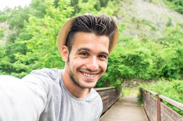 Facet bierze selfie ze swoim smartfonem w parku - ludzie, styl życia i koncepcja technologii