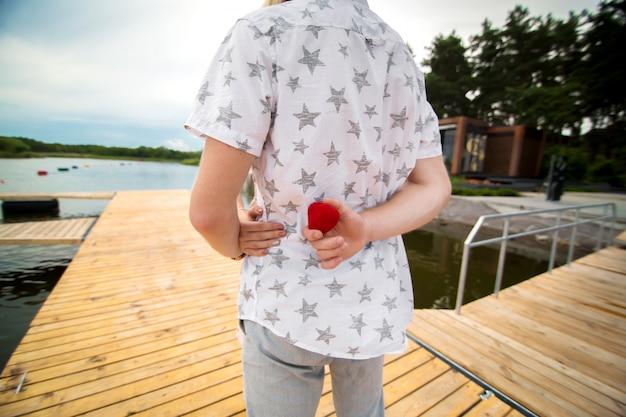 Facet chce wyciągnąć rękę i serce do swojej ukochanej dziewczyny. ukrywa pudełko z obrączką za plecami. niespodzianka, na którą czeka każda dziewczyna