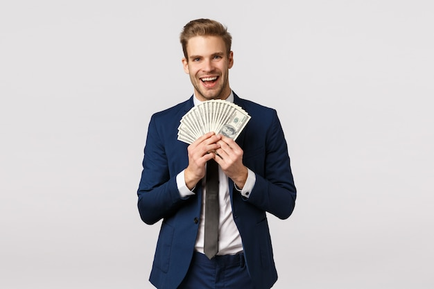 Facet chwalący się pieniędzmi. atrakcyjny blond brodaty biznesmen w klasycznym garniturze, trzymający dużo gotówki, pokazujący dolary i uśmiechnięty zadowolony, wygrał na loterii, zakład sportowy, stojący białe tło zadowolony