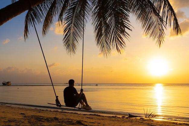 Facet cieszy się zachodem słońca, jeżdżąc na huśtawce na tropikalnej plaży.