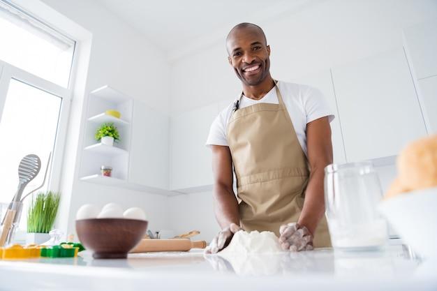 Facet cukiernik robi świeży miękki chleb robi ciasto z mąki jajka kulinarne w nowoczesnej kuchni wewnętrznej