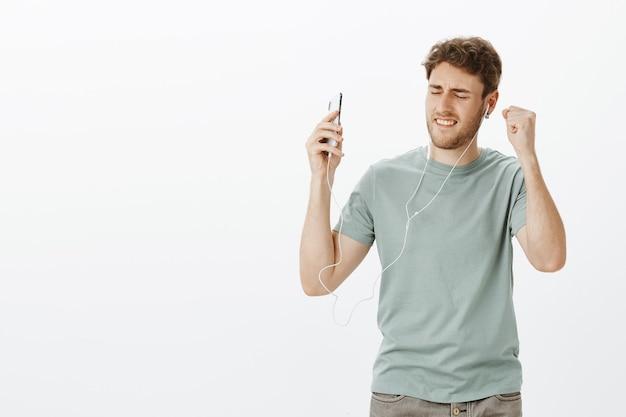 Facet czuje zastrzyk energii dzięki muzyce w słuchawkach. portret zadowolony relaksujący przystojny mężczyzna tańczy z zamkniętymi oczami podczas słuchania piosenek w słuchawkach